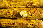 Top vie of grilled corn and pieces of butter.Natural sun light