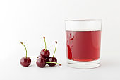 Closeup of glass of sweet cherry beverage nad pile of cherries on the white background