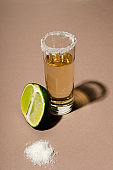 One glass of tequila, half of lime and heap of salt on the brown surface.Vertical image