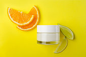 Vertical image.Glass jar of facial cream and fresh juicy fruits on the yellow background