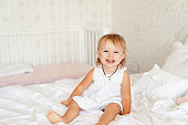 little girl on bed in bedroom and laughs. happy childhood.