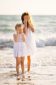 kids girls cover face with hands and walking on sea beach with big waves.