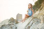 little girl sitting on rock at sunset. travel.