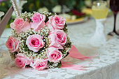 pink ribbon .pink engagement flowers on white table . Bride and groom with Engagement gold rings put on the pink wedding bouquet . Pink engagement bouquet .