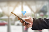 Hand holding using mobile smartphone with wifi icon