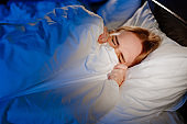 a woman lies in bed under a white blanket and afraid, frightened.