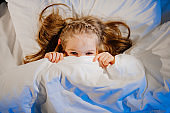 top View. Little girl lies in bed, frightened and covers face with blanket