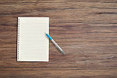 Blank white notebook pad on wood desk background