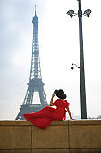 woman in red dress and hat sits alone in front of Eiffel tower in Paris.