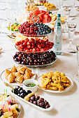 table served with light summer snacks-fruits, vegetables, berries. catering