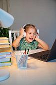 small girl in headphones listens music on laptop