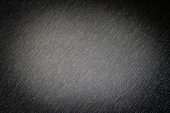 Abstract horizontal diagonal gloomy dark gray black vignetted empty rough monochrome background with textile fabric surface texture in horror style, copy space for text, spot of light in the center