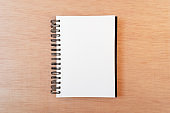 Blank notebook, ring binder, in wooden background. Flat lay, copy space, top down perspective