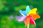 Colorful Pinwheel Toy Against green bokeh background of summer.