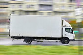 Side view of a cargo delivery truck blurred with an copy space on a blurred background in traffic