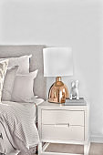 Bedroom with pillows and small cupboard with a gold  lamp