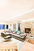 Living room with pillows and leather sofas under bright lights