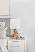Modern bedroom with gold color table lamp on the cabinet