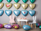 A wall of balloons in the form of hearts of different colors.