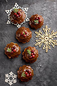Christmas chocolate cupcakes, with icing, are decorated with a sprig of spruce, and cranberries. On a dark table dessert, with cinnamon sticks, snowflakes, serpentine. Holidays content