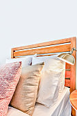 Luxury wooden bed with pillows close up beside a lamp