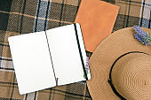 Summer rest mock up with hat and diary on a plaid mat, outdoor flat lay photo