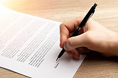 Businessman hand's signing legal or insurance document.