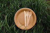 Eco-friendly natural plate with spoon, fork, knife. Set of disposable ecological dishes on green grass background. Sustainability of planet. Cardboard dishes made of fiber of bamboo and bagasse