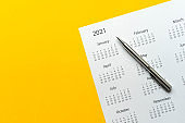 close up top view on white calendar 2021 schedule on yellow color background to make appointment meeting or manage timetable each day for design planning work and life concept