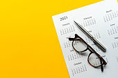 close up top view on white calendar 2021 schedule with pen and eyeglasses on yellow color background to make appointment meeting or manage timetable each day for design planning work and life concept