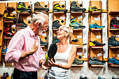 Elderly couple in love enjoying shopping for rock climbing shoes in an outdoor activities store