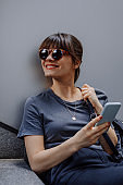 Using Technology on the Go: a Smiling Woman with Sunglasses Using her Smartphone on the Street