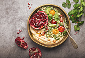 Rustic bowl with couscous salad with vegetables, hummus and fresh cut pomegranate. Middle eastern or Arab style meal with seasonings and fresh cilantro. Healthy Mediterranean dinner, toned image