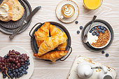 Beautiful morning breakfast with fresh croissants, granola with yoghurt and berries, toasts, coffee cappuccino and fruit on plate. Tasty and healthy breakfast on white wooden table, top view