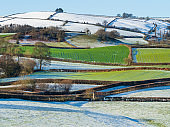 Snow and green grass on colourful fields of Shropshire Hills, near Clun in December. Photo of a beautiful hilly British landscape in UK