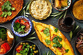 Traditional Turkish food, assorted dishes and mezze appetizers on rustic background from above. Pide, Lahmacun, meat kebab, Turkish meatballs, sweet baklava and Künefe. Middle East cuisine, top view