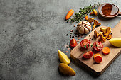 Fresh cherry tomatoes, potatoes, mushrooms chanterelles, carrot, herbs on cutting board and wooden cooking spoon with olive oil. Food cooking background with ingredients, top view, space for text