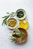 Green and black olives with olive oil in a glass bottle, olive tree sprigs and cut fresh ciabatta bread on wooden cutting board. White rustic background, mediterranean food concept, top view