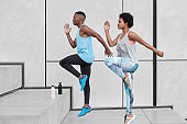 Hard sport concept. Motion shot of two black female and male run up steps, demonstrate good ability of climbing high, have bottles with fresh water to prevent dehydration, move against white wall