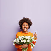 Happy lovely woman with crisp hair, points above on copy space, smiles tenderly, holds white tulips, being in good mood, isolated over purple background. People, flowers, advertisement concept
