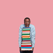 Vertical shot of stupefied black man leans head on pile of books, wears round glasses, surprised with many tasks for seminar, cramms material, models over pink studio wall with free space above