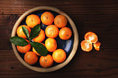 Flat lay image of a plate of fresh picked Mandarin Oranges in a rustic wood table with one peeled piece of fruit with warm side light.