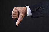 Businessman hand giving the thumbs down signal closeup