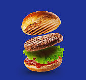 Burger Levitation. Hamburger with beef, ketchup and salad. A sandwich is flying. Burger on a blue background.