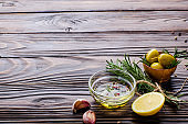 Food background frame made of oils condiments and spices on kitchen table. Cooking concept