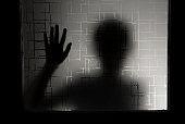 Dark silhouette of girl behind glass. stock photo