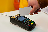 A man pays at the checkout using a credit card through a wireless payment terminal.
