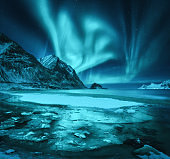 Northern lights and snowy mountains, frozen sea coast and reflection in water in Lofoten islands, Norway. Aurora borealis. Winter landscape with polar lights, ice in water. Starry sky with aurora