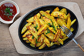 Fried potatoes in a rural style, with spices and ketchup. On rustic pan, on a wooden table