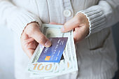 Woman wear a knit sweater hands holding counting money Dollar bill with credit card and light bokeh - Business concept.